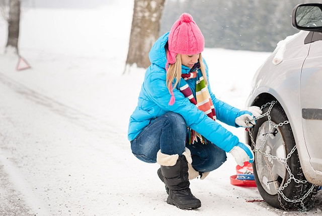 Woman putting chains on her tires in snow.
