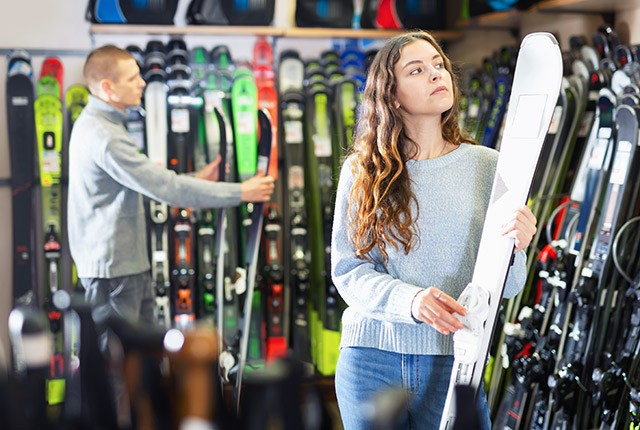 Ski shop girl holding skis.